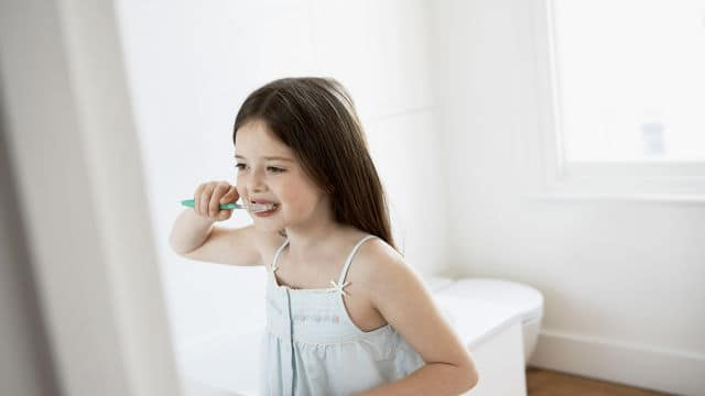 a little girl brushing her teeth in the bathroom