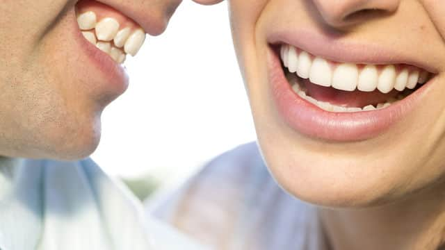 a close-up of a man and woman healthy teeth smiling