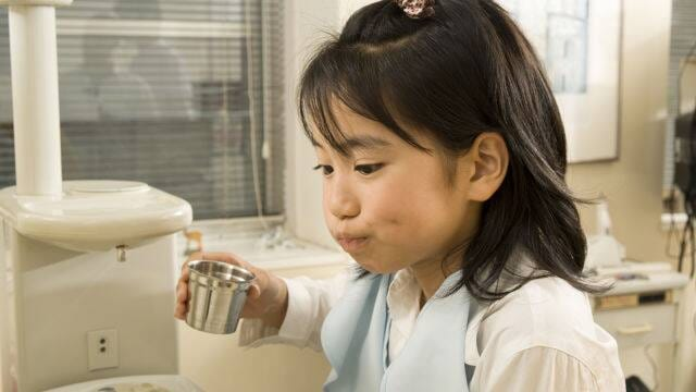 child cleaning teeth during dental exam