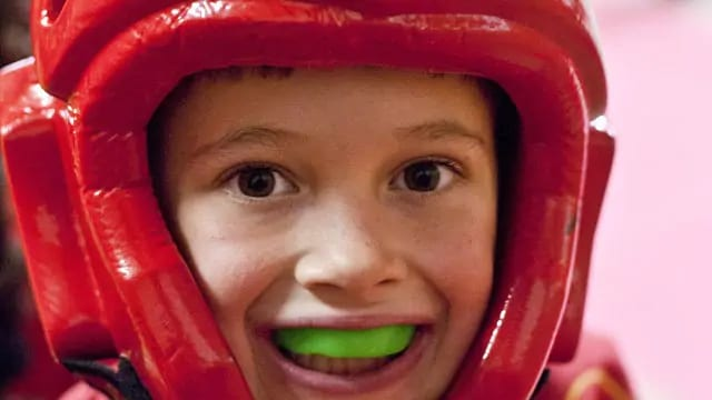 kid wearing a green mouthguard