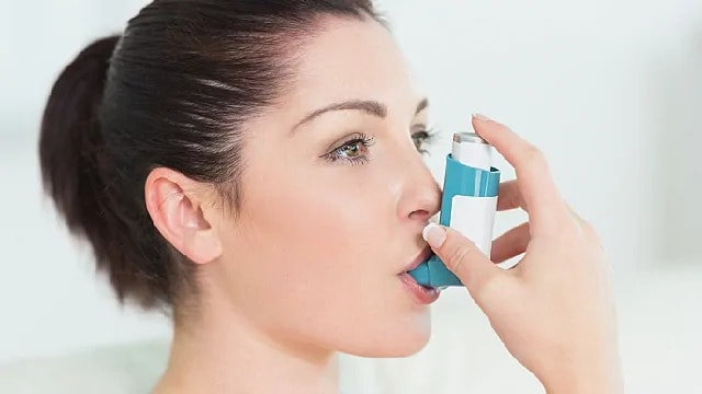 woman using inhaler to aid breathing