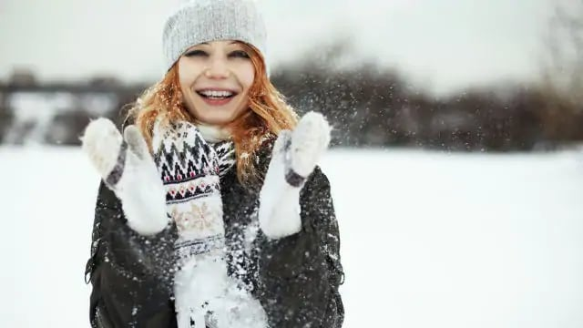 woman smiling in the snow after tooth swelling treatment