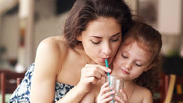 mother and daughter drinking water to promote good oral health