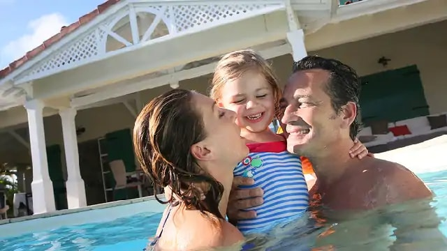 A smiling couple holding a child in a pool
