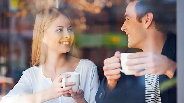 A couple smiling while holding coffee cups