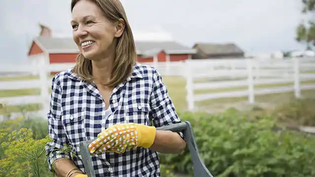 woman smiling while picking vegetables