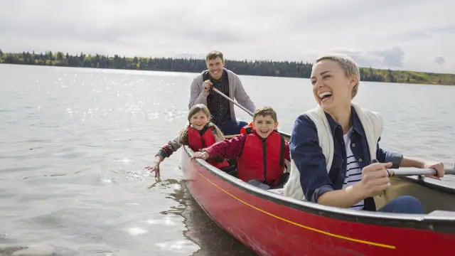 A smiling family of four canoeing on a body of water