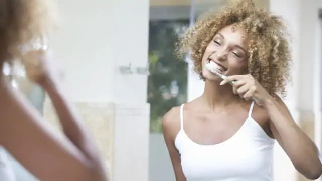 woman smiling while brushing her teeth