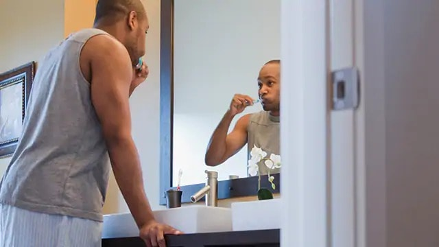 man brushing teeth after using oral health probiotics