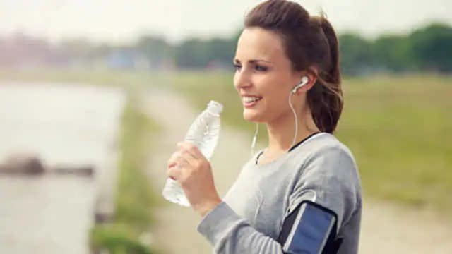 person drinking water to alleviate dry mouth on a run