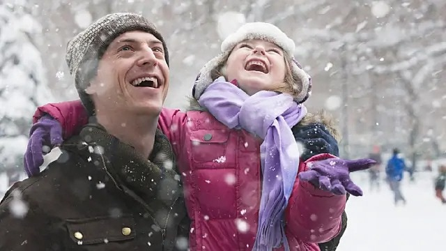 father and daughter laughing in the snow