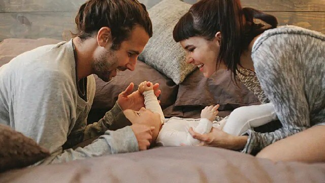 parents playing with their newborn baby
