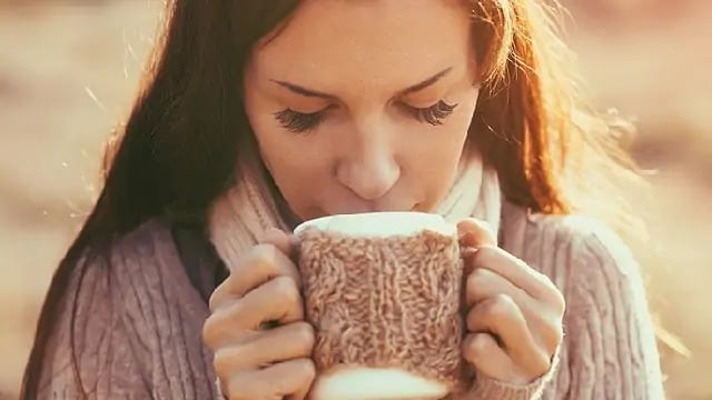 woman drinking tea to help with sore throat