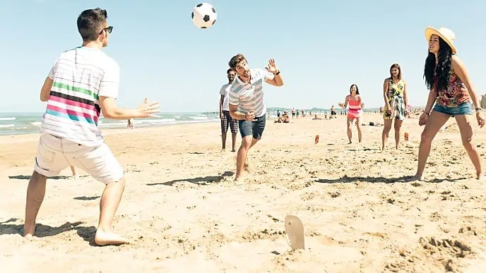 people playing soccer on the beach