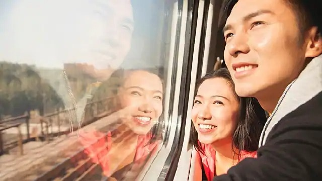Smiling couple looking through a train window