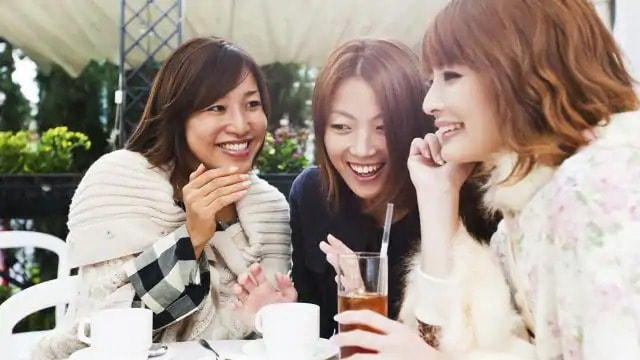 Three women smiling while having drinks at a table