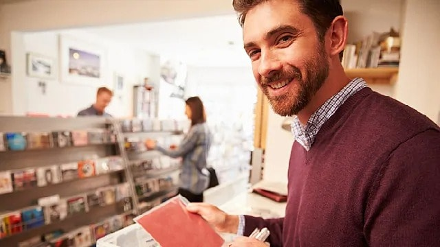 Man smiling while holding a greeting card