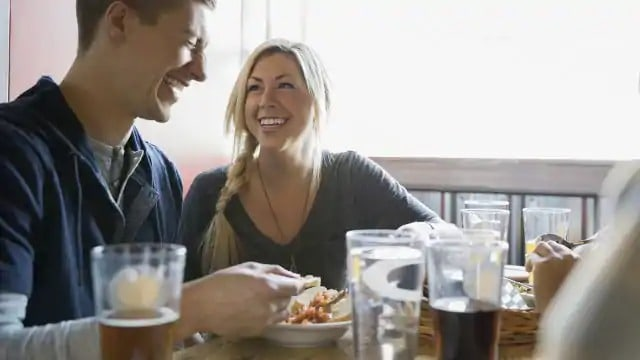 A smiling woman looking at a laughing man during a meal