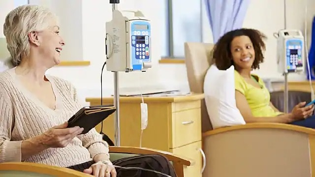 Two women conversing during chemotherapy