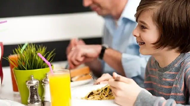 Child with braces smiling during a meal