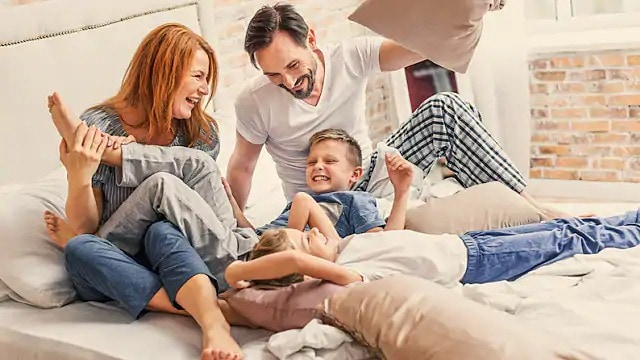 Family of four laughing while playing with pillows