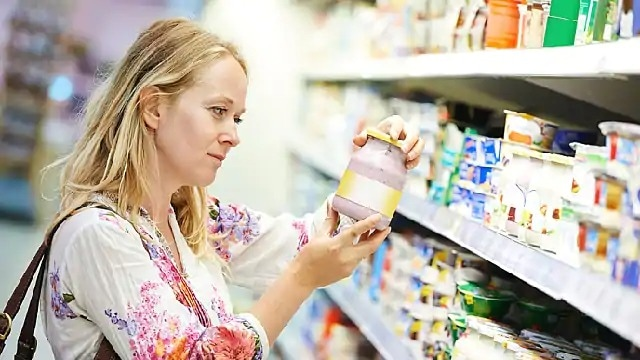 A woman reading the label on a jar of food