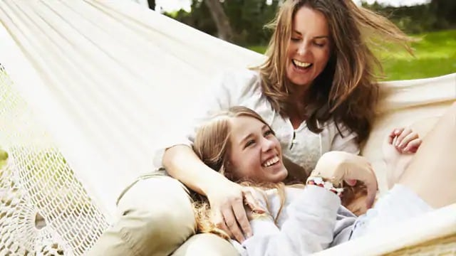 Two women smiling while lounging in a hammock