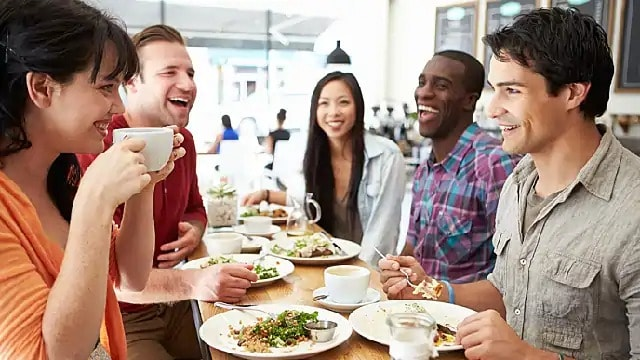 A group of people smiling while having a meal