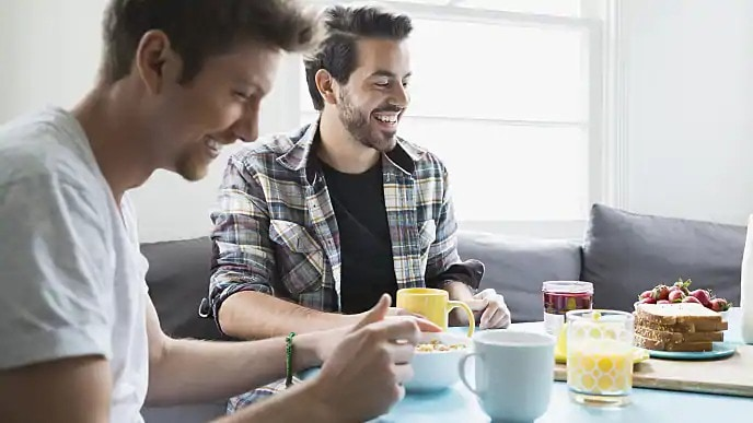 Two men smiling while sitting down for breakfast
