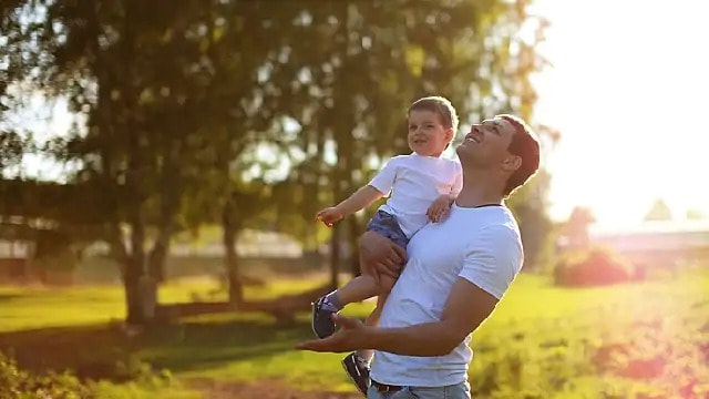 A smiling man outside, holding a child while looking up