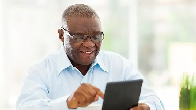 A man with glasses smiling while using a tablet