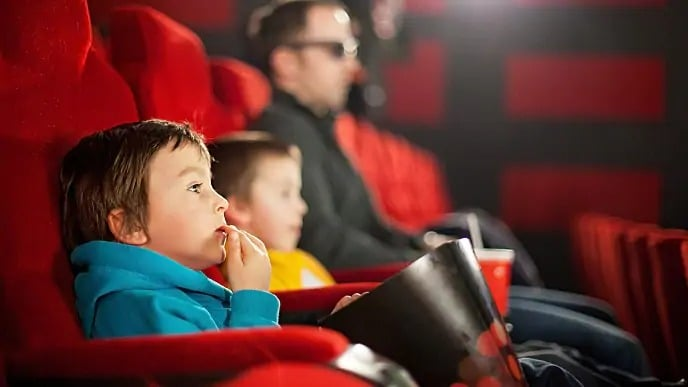 Children eating popcorn in a movie theater