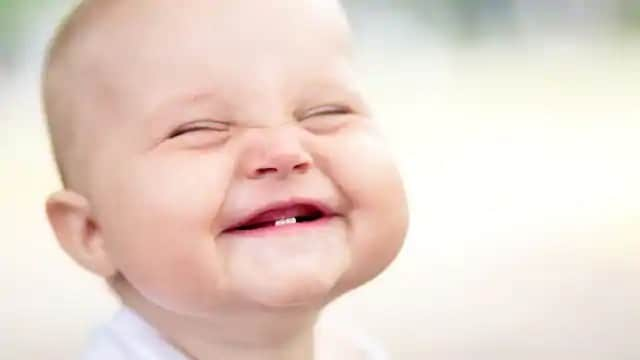 Infant smiling with first signs of new teeth coming in