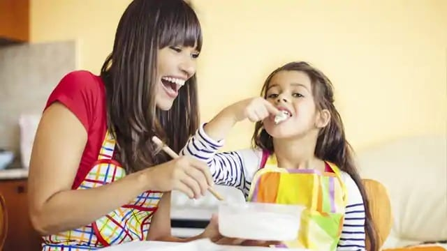 A smiling woman letting a child taste food