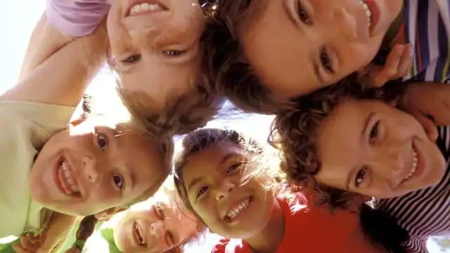 Six children smiling and looking down at the camera