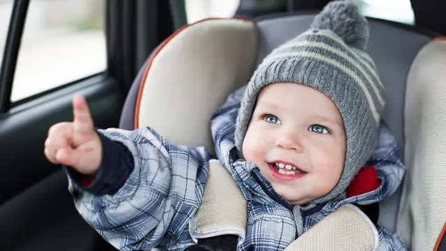 Young smiling child in a car seat