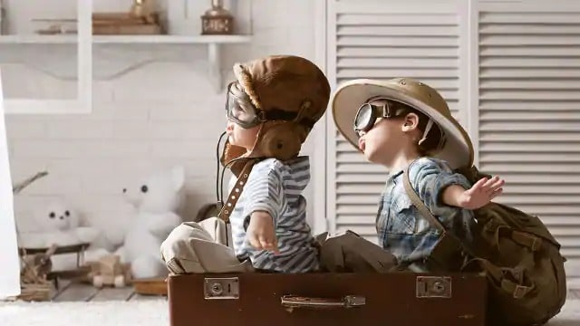 Two children playing and sitting in a suitcase like pilots