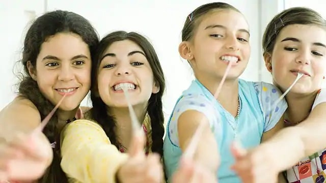 Four young girls pulling gum from their mouths