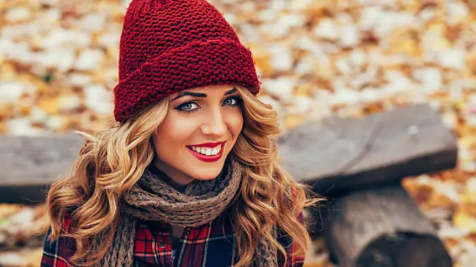 A woman wearing a knitted hat smiling