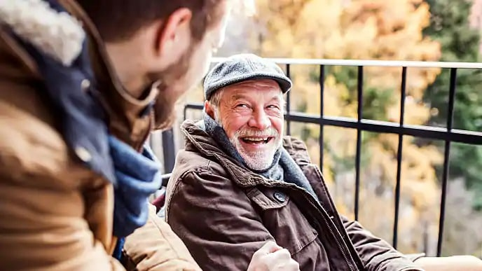 older man smiling outside