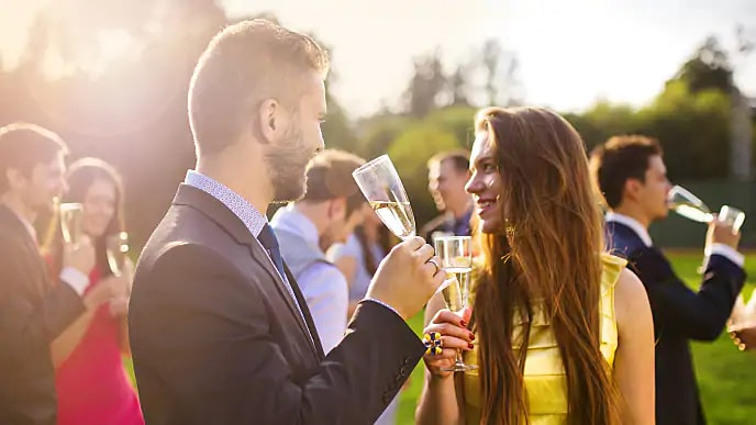 A smiling couple holding champagne glasses at an outdoor event