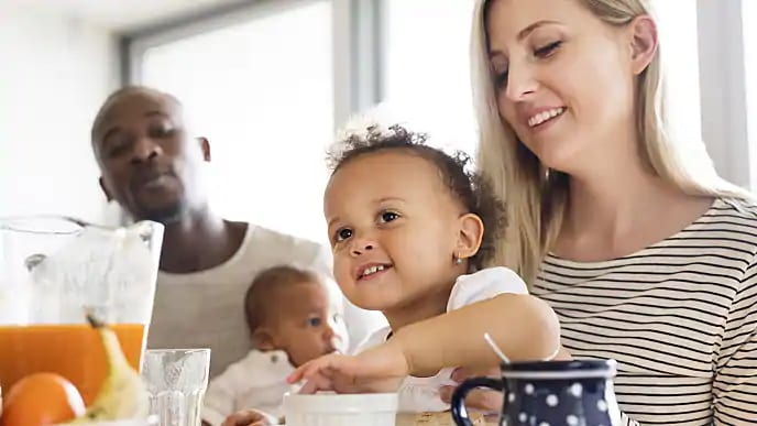 A smiling couple, each holding small children during breakfast
