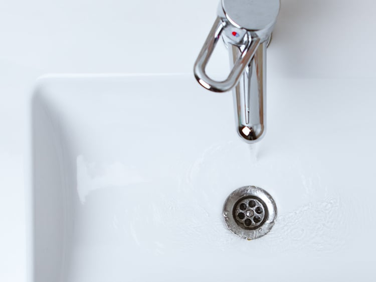 water running down the drain of a sink