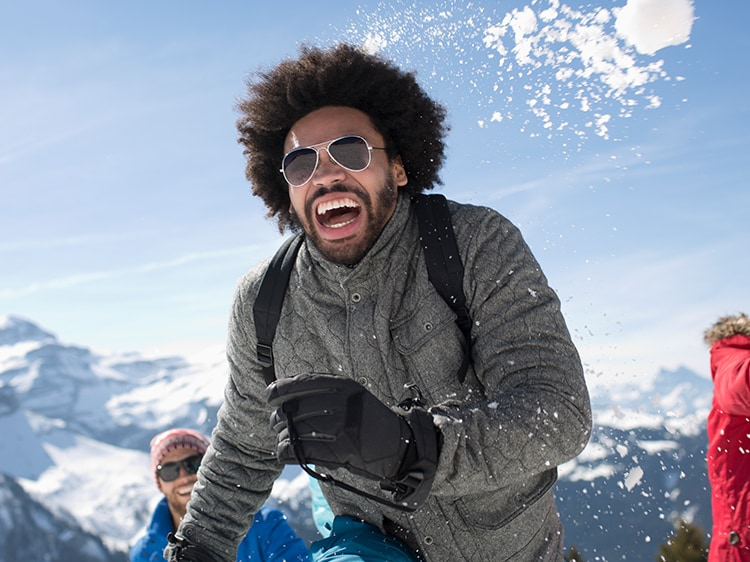 man smiling while playing in snow