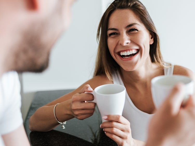 smiling woman holding a coffee cup