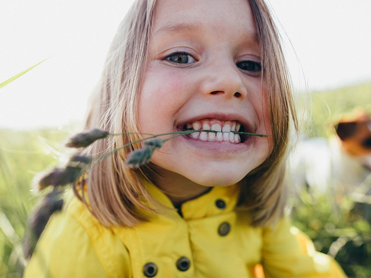 toddler smiling with wheat between teeth