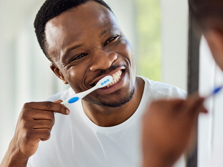man brushing with colgate toothbrush