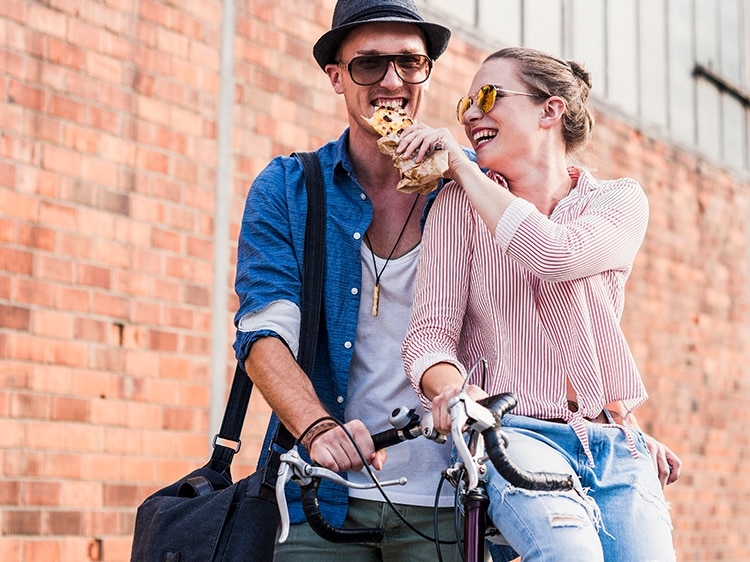 A happy young couple eating pizza and walking with a bicycle