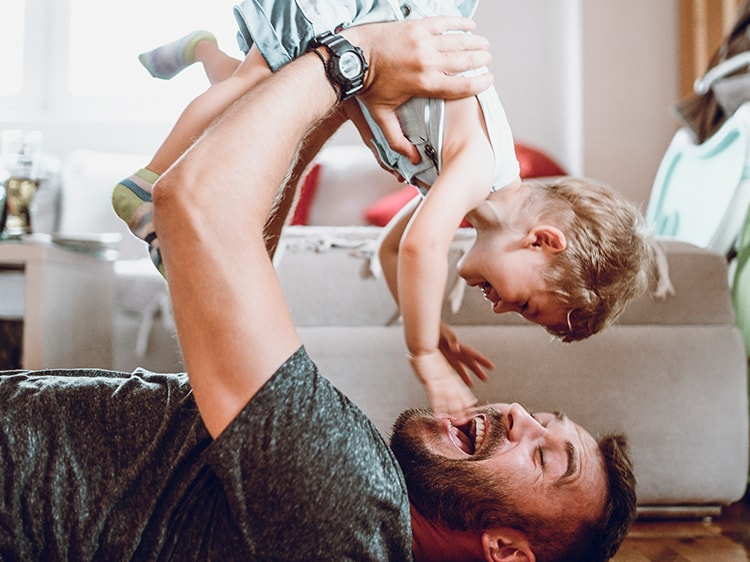 smiling man holding a toddler in the air
