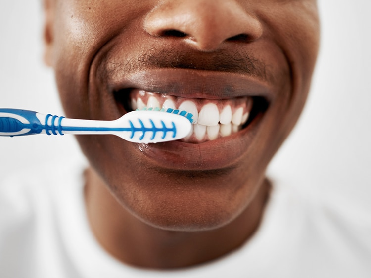 man brushing teeth with colgate toothbrush